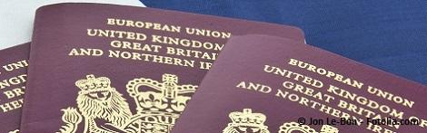 Three United Kingdom passports on folded Union Jack Flag